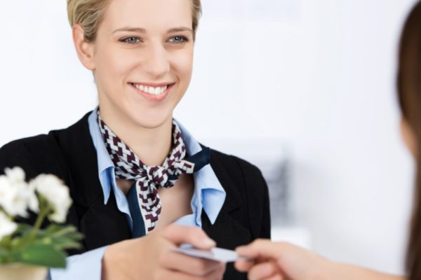 Empfangsdame übergibt Ausweis an Besucher
