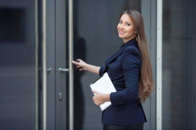 Frau an Eingangstür Besuchermanagement