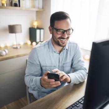 Mann im Home Office vor PC mit Smartphone in der Hand