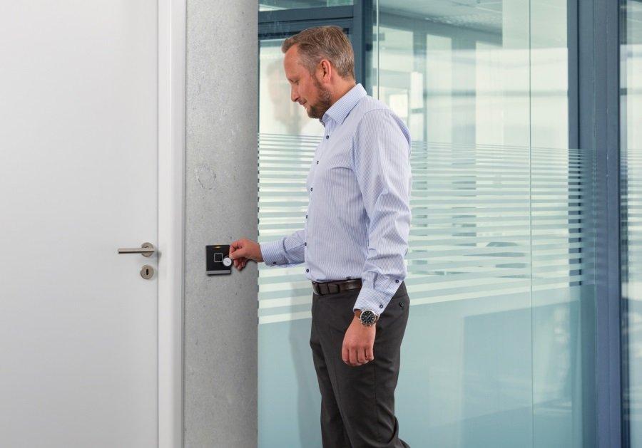 Mann mit RFID Ausweis an Zutrittsleser