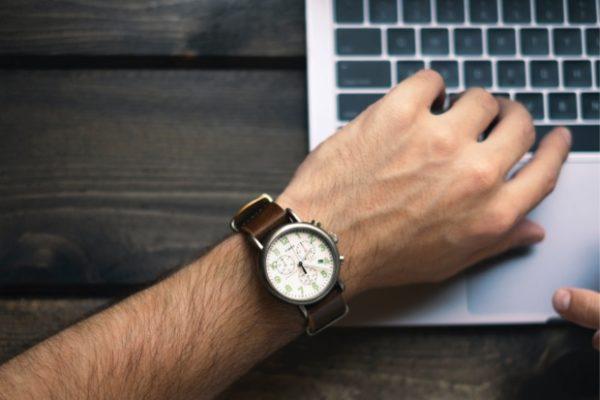 Hand mit Armbanduhr im Hintergrund die Tastatur eines Laptops